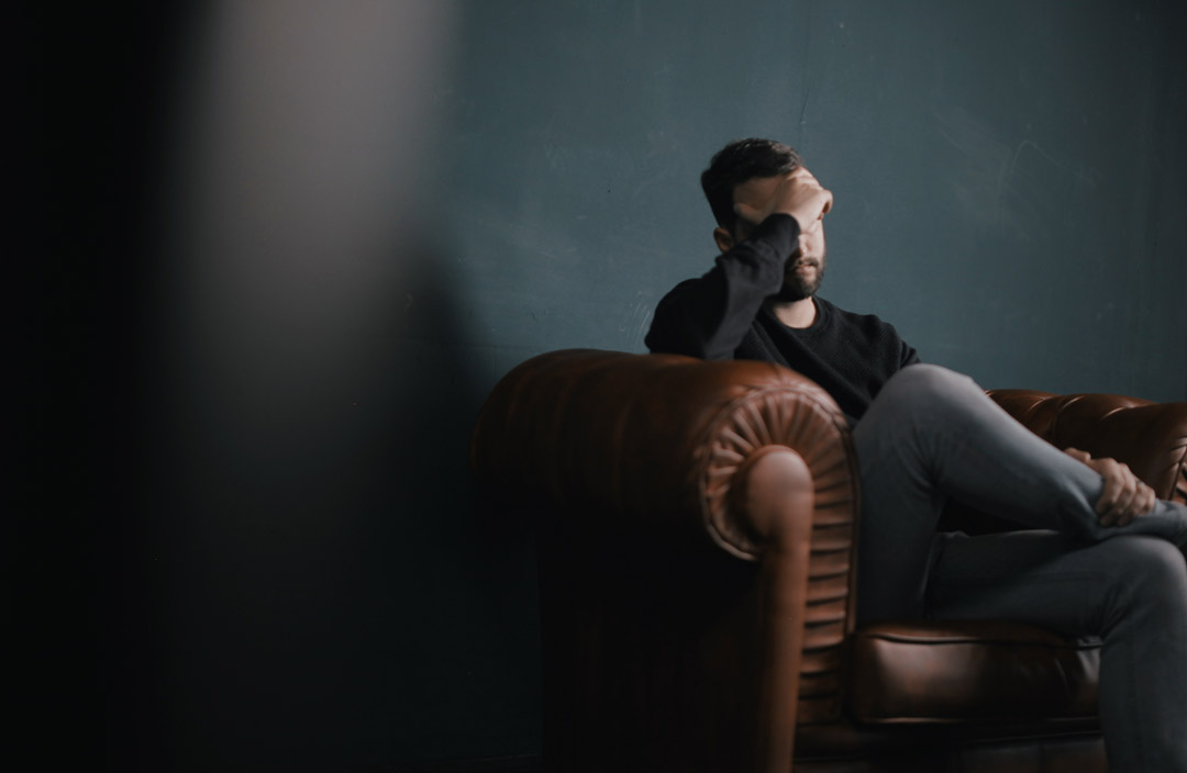 abattoir-man-thinking-sitting-on-sofa-against-wall